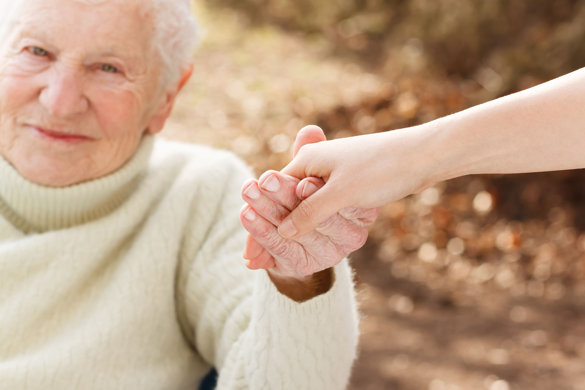 Elderly Woman Holding Hand of Helper